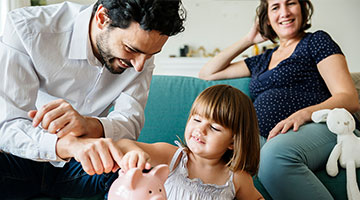 Dad helping child put money in piggy bank